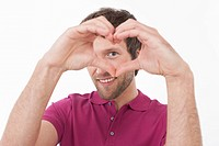 Mid adult man making heart shape, smiling, portrait (thumbnail)