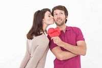 Man with heart shaped gift box, woman kissing him