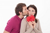 Woman with heart shaped gift box, man kissing her (thumbnail)