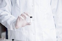 Germany, Bavaria, Munich, Scientist holding phial for medical research in laboratory