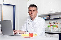 Germany, Bavaria, Munich, Scientist with laptop in laboratory, portrait