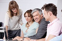 Germany, Bavaria, Munich, Men and women using laptop in office