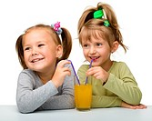 Two Little girls are drinking orange juice from one glass using straw, isolated over white