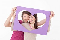 Couple looking through heart shaped frame (thumbnail)