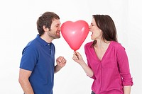 Couple with heart shaped balloon, smiling