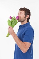Mid adult man smelling flowers, smiling