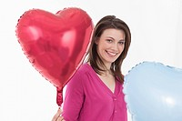 Young woman holding heart shaped balloons, portrait
