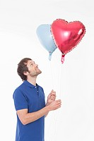 Mid adult man looking at heart shaped balloons, smiling