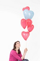 Young woman looking at heart shaped balloons