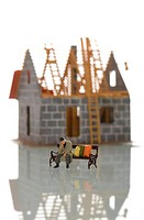 Miniature figure of a homeless person sitting on a bench in front of a unfinished house under construction, symbolic image of poverty due to high cons...