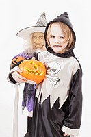 Brother and sister in fancy dress costume with halloween lantern, portrait