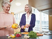 Germany, Cologne, Senior women cutting vegetable in nursing home, smiling