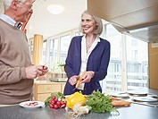 Germany, Cologne, Senior couple cutting vegetables, smiling