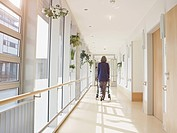Germany, Cologne, Senior woman with walking frame at corridor in nursing home