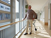Germany, Cologne, Senior man standing in corridor of nursing home, walking frame in background