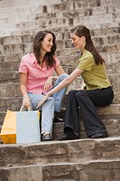 Two women with shopping bags sitting on steps