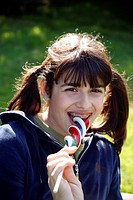 Teenage girl licking a lollipop (thumbnail)