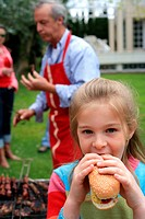 Young girl eating a hot dog