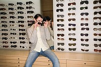 Woman posing in front of sunglasses display (thumbnail)