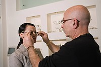 Woman having glasses fitted by optometrist