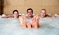 One man with two women in jacuzzi at a spa