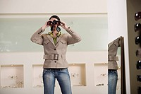 Woman with binoculars in eyeglass store