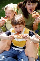 Three children eating pizza