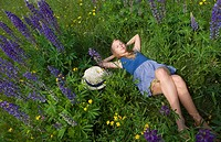 Austria, Teenage girl relaxing in lupine field