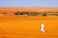 Arabischer Mann wandert im Wüstensand vor einer Oase, Sahara, Libyen / Arab man strolling in the Sahara desert near an oasis, Libya