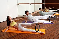 Young man and woman performing a pilates exercise (thumbnail)