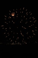 Fireworks exploding, with town lights of Umbrian valley in distance, Italy