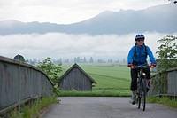 Germany, Bavaria, Kochel, Mature man riding bicycle
