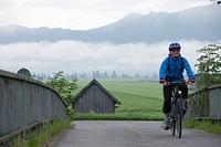 Germany, Bavaria, Kochel, Mature man riding bicycle