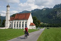 Germany, Bavaria, Fuessen, Mature man riding bicycle with church in background