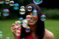 Mid twenties brunette woman blows bubbles in the park