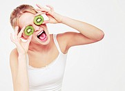 Young woman covered her eyes with pieces of kiwi and shouting
