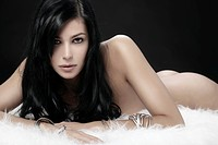 Naked young woman lying on white fur, beauty shot