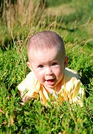 happy smiling baby crawling in green grass