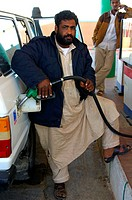 Libyscher Mann in traditioneller Kleidung betankt sein Fahrzeug an einer Tankstelle in Al Awaynat Libyen / Libyan man in traditional clothes filling p...
