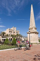 Spain, Menorca, Man and woman cycling through Ciutadella
