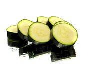 green zucchini slices on a white background water drops