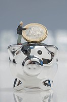 Male figurine with euro coin on top of piggy bank
