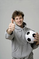 Young man holding soccer ball and showing thumbs up