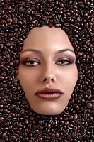 face shot of a pretty girl immersed in coffee beans