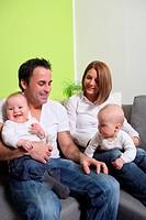 Junge familie mit Babys _ Zwillinge. Die Eltern und die babys lachen freundlich und glücklich.Young families with babies _ twins. The parents and the ...