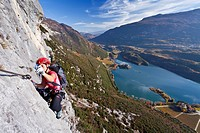 Climber ascending Rino Pisetta Climbing Route in Sarchetal Valley above Lake Toblino, Lake Garda region, Trentino, Italy, Europe