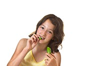 Young Girl eating crisp cucumber on white background