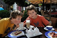 Two youths, 13 and 15, sitting in a cafe with cake