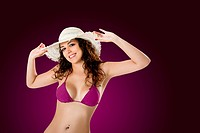 Portrait of a beautiful young woman in bikini posing on a violet background
