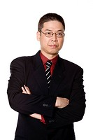 Studio portrait of middle aged Asian businessman wearing glasses with arms crossed on white background